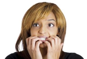 Closeup portrait of young unhappy woman biting her nails and looking to side with a craving for something or anxious worried isolated on white background. Negative emotion facial expression feelings