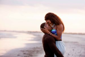 Couple on beach, hugging, face to face