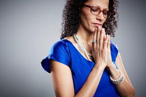 Studio portrait of mature woman praying