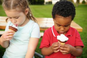 Little Boy and Girl Eating Ice Cream Cones Outside