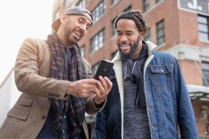 Smiley homosexual couple taking selfie with smart phone in street