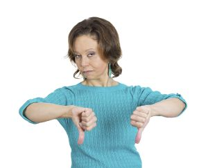 Closeup portrait, unhappy business woman, wife, giving thumbs down sign gesture looking with negative expression and disapproval, isolated white background. Human emotion facial expression, feeling