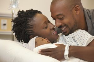 Black couple in hospital looking at newborn baby