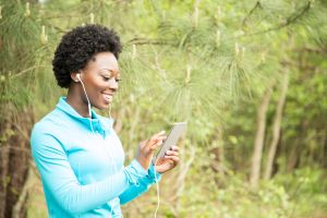 One African descent woman exercising, using cell phone in neighborhood park.