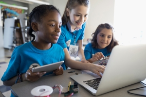 Pre-adolescent girls programming electronics at laptop and digital tablet in classroom