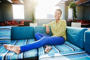 Black woman laughing on rooftop sofa