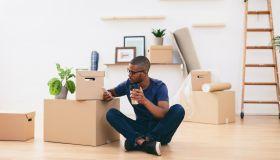 Young man sitting beside cardboard boxes having a coffee break