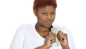 Closeup portrait of grumpy greedy miserly young woman, protecting money, holding dollar bills in hands, looking anxiously with suspicion, isolated white background. Negative human emotions expressions