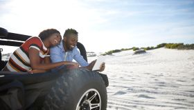Couple with digital tablet in jeep on beach