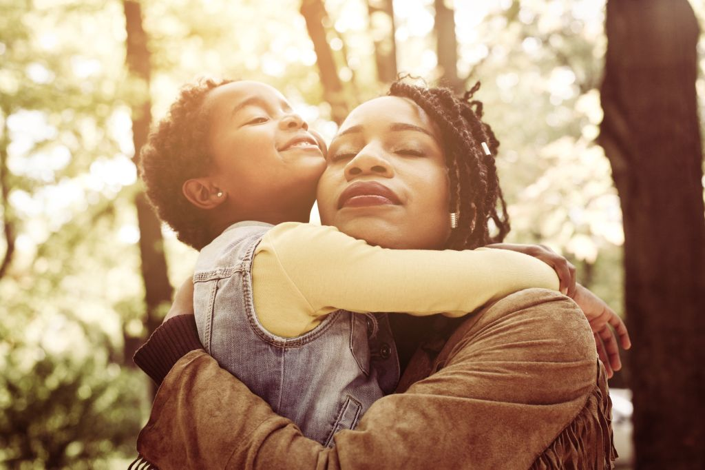 African American mother and her daughter hugging with daughter in forest.