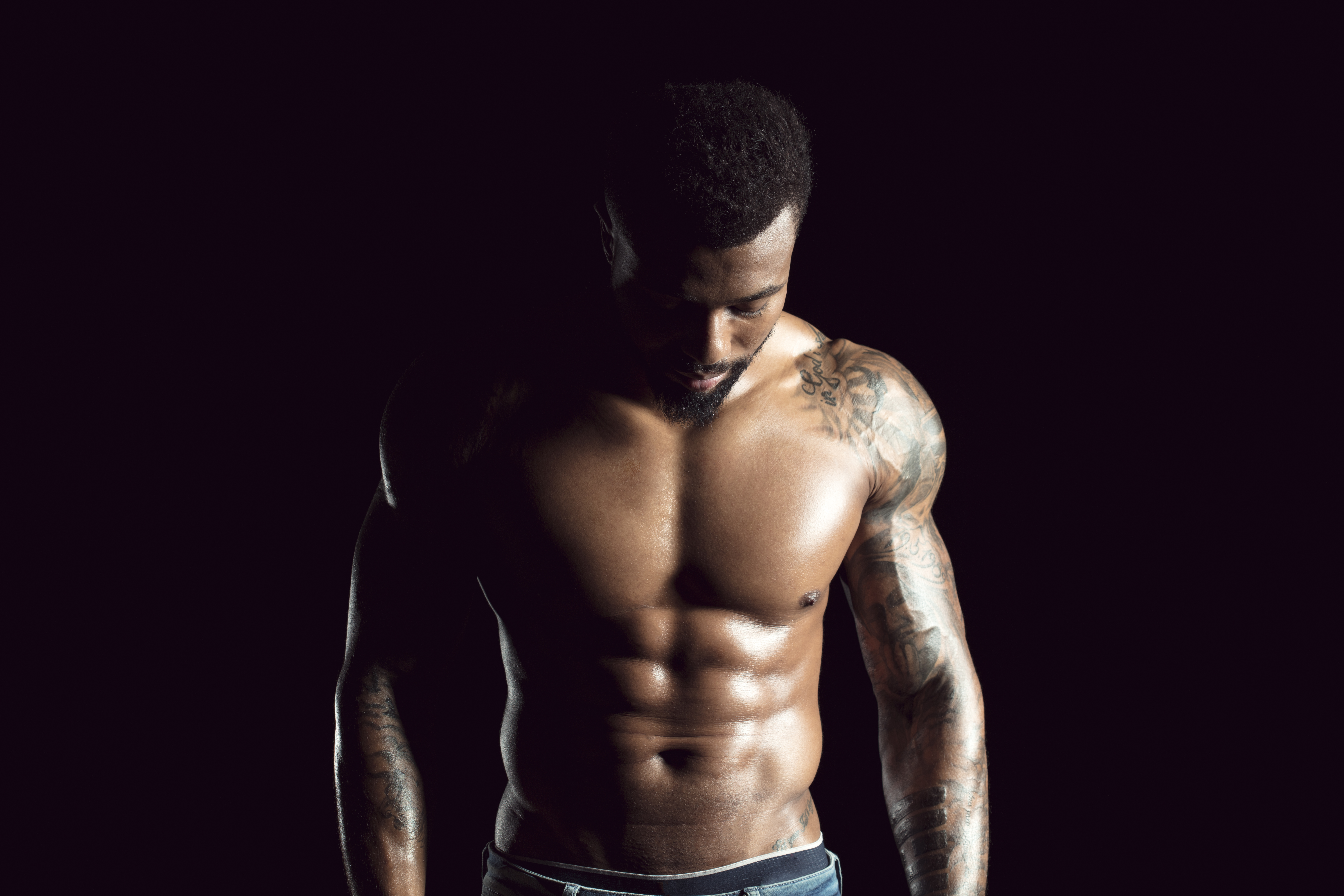 Tattooed physical athlete in front of black background