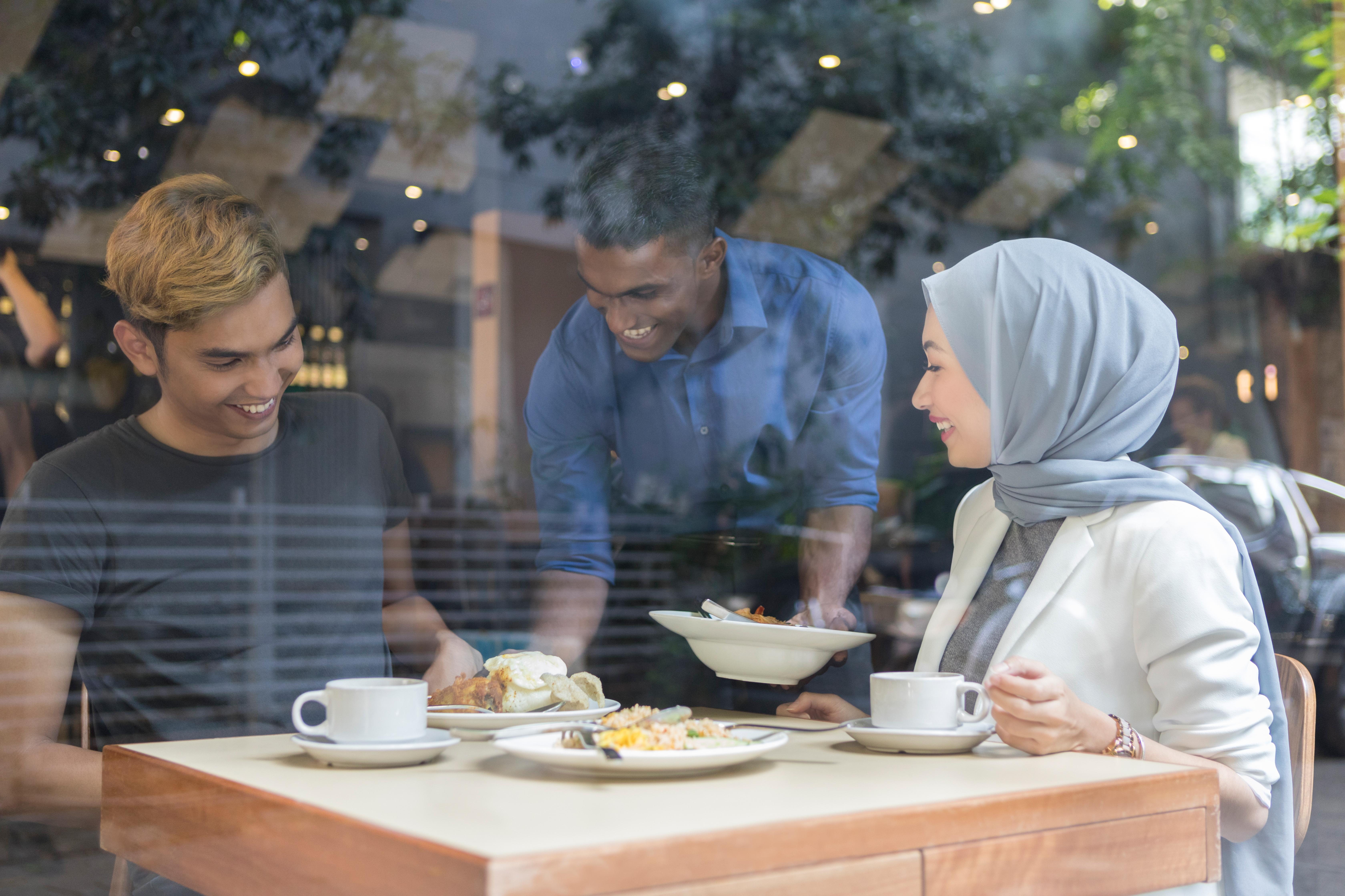 Young Malaysian couple enjoys restaurant breakfast